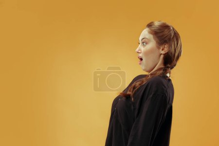 Photo for Why is that. Beautiful female half-length portrait isolated on trendy gold studio backgroud. Young emotional surprised, frustrated and bewildered woman. Human emotions, facial expression concept. - Royalty Free Image
