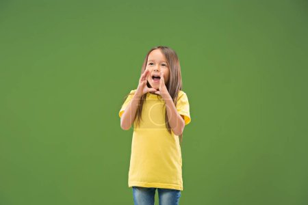 Photo for Do not miss. Young casual teen girl shouting. Shout. Crying emotional teenager screaming on studio background. Female half-length portrait. Human emotions, facial expression concept. Trendy colors - Royalty Free Image