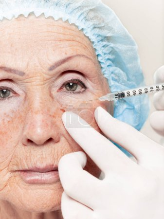 Photo for The surgeon doing skin check on mid age woman before plastic surgery. Senior female model. plastic surgery, lifting, aging concept - Royalty Free Image