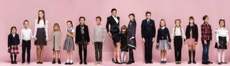 Photo pour Mignon souriant heureux enfants élégants et enseignante sur fond rose. Belle adolescente élégante et garçon debout ensemble et posant au studio. Style classique. Mode et émotions pour enfants concept - image libre de droit