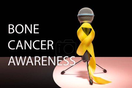 Photo pour Couleur symbolique de ruban jaune pour prévention suicide et de sensibilisation du cancer de Sarcome osseux avec microphone. Le cancer, santé, aide, soins, aide, espoir, maladie, concept de soins de santé - image libre de droit