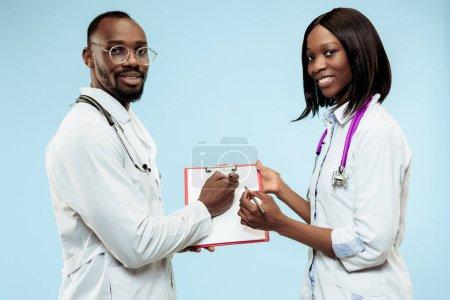 Photo pour La femelle et le mâle souriant heureux médecins américains afro sur fond bleu au studio. La clinique, médecin, infirmière, santé, soins de santé, hôpital, soins, travail, concept professionnel - image libre de droit