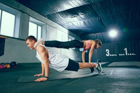 Photo for Shot of young man and woman standing in plank position at the gym. Functional fitness workout. Couple during training session. Fit athletic models. Healthy lifestyle concept - Royalty Free Image