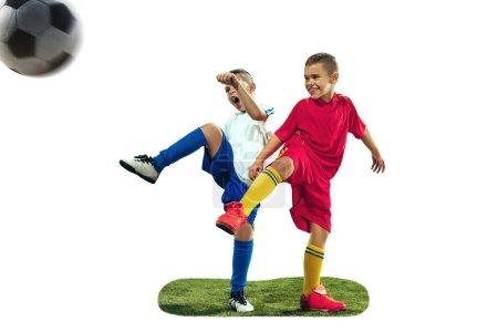 Foto de Jóvenes muchachos patea la pelota de fútbol. Foto aislado sobre fondo blanco. Jugadores de fútbol en movimiento sobre fondo de estudio. Forma niños en acción, salto, movimiento en el juego - Imagen libre de derechos