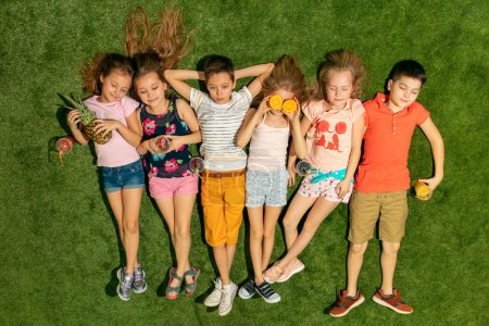 Photo for Group of happy children playing outdoors. Kids having fun in spring park. Friends lying on green grass. Top view portrait - Royalty Free Image