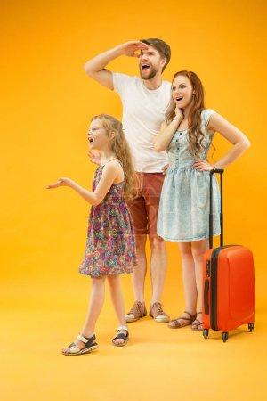 Photo pour Joyeux parent avec sa fille et sa valise au studio isolé sur fond jaune. Voyages, vacances, parentalité, convivialité, concept touristique . - image libre de droit