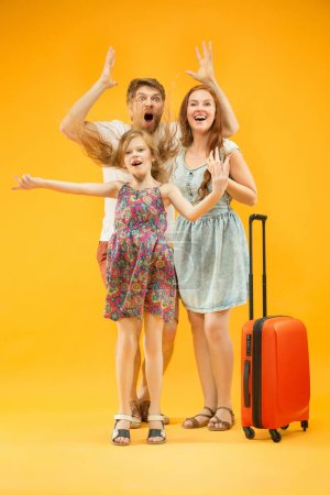 Photo for Happy surprised parent with daughter and suitcase at studio isolated on yellow background. Travel, vacation, parenthood, togetherness, tourism concept. - Royalty Free Image