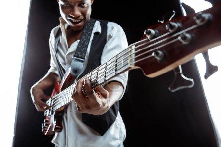 Photo pour Musicien de jazz beau afro-américaine jouant guitare basse en studio sur fond noir. Concept musical. Jeune homme attrayant joyeux improvisation. Rétro portrait gros plan. - image libre de droit
