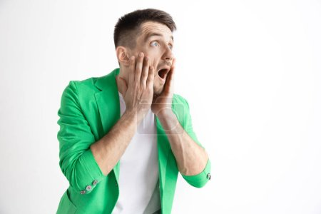 Photo pour Wow. Attrayant mâle demi-longueur front portrait sur fond gris studio. Jeune homme surpris émotionnel permanent avec la bouche ouverte. Émotions humaines, notion de l'expression du visage - image libre de droit
