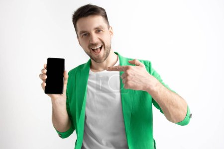 Photo for Its cool. Good news. Do that like me. Young handsome man showing smartphone screen and signing OK sign isolated on gray background. Human emotions, facial expression, advertising concept. - Royalty Free Image