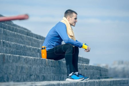 Photo for Man resting after running on city background at morning. Healthy lifestyle concept. - Royalty Free Image