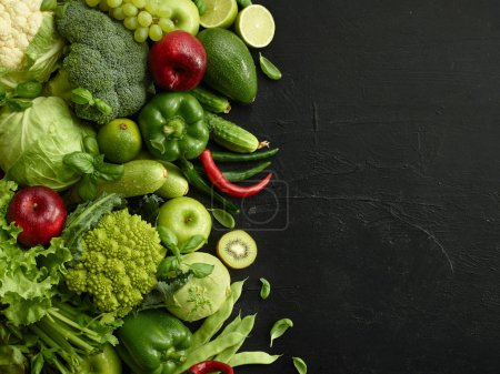Photo for Healthy food dish on black stone background. Healthful set including vegetables and fruits. Grape, apple, kiwi, pepper, lime, cabbage, zucchini, grapefruit. Proper nutrition or vegetarian menu. - Royalty Free Image