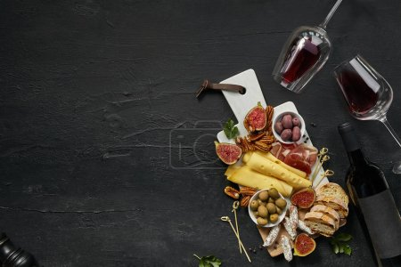 Photo pour Deux verres de vin rouge et une assiette de fromage savoureuse avec des fruits, du raisin, des noix et du pain grillé sur une plaque de cuisine en bois sur le fond de pierre noire, vue sur le dessus, espace de copie. Aliments et boissons gastronomiques . - image libre de droit