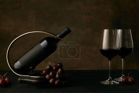Photo pour Vue de face de raisins savoureux avec la bouteille de vin et des verres sur fond sombre studio, copier l'espace pour insérer votre texte ou image. Aliments et boissons gastronomiques . - image libre de droit