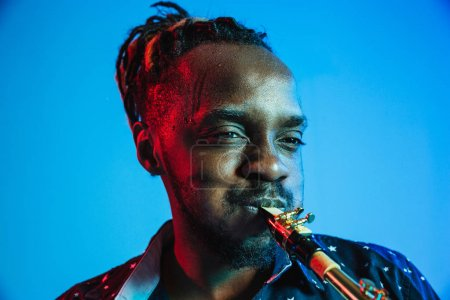 Photo for Young african-american jazz musician playing the saxophone on blue studio background in trendy neon light. Concept of music, hobby. Joyful attractive guy improvising. Retro colorful portrait of artist - Royalty Free Image