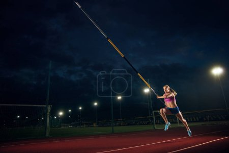 Photo for Ready to overcome difficulties. Professional female pole vaulter training at the stadium in the evening. Practicing outdoors. Concept of sport, activity, healthy lifestyle, action, movement, motion. - Royalty Free Image