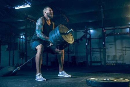 Photo pour Jeune athlète homme en bonne santé faisant de l'exercice avec le haltère dans la salle de gym. Modèle masculin unique s'entraînant dur et pratiquant dans les fentes. Concept de mode de vie sain, sport, fitness, musculation, crossfit . - image libre de droit