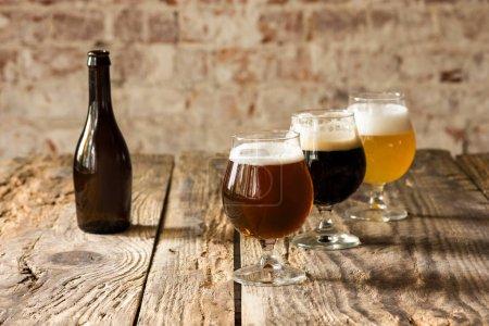 Lunettes de différents types de bière sur fond en bois