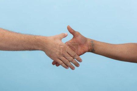 Photo pour Gros plan d'humains tenant la main isolés sur fond bleu studio. Concept de relations humaines, d'amitié, de partenariat, d'entreprise ou de famille. Espace de copie . - image libre de droit