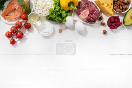 Photo for Ketogenic low carbs diet - food selection on white background. Balanced healthy organic ingredients of high content of fats for the heart and blood vessels. Meat, fish and vegetables. Copyspace. - Royalty Free Image
