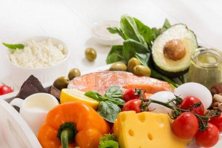 Foto de Dieta cetogénica baja en carbohidratos - selección de alimentos sobre fondo de madera blanca. Ingredientes orgánicos saludables equilibrados de alto contenido de grasas. Nutrición para el corazón y los vasos sanguíneos. Carne, pescado y verduras - Imagen libre de derechos