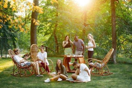 Photo pour Groupe d'amis heureux mangeant et buvant des bières au barbecue le soir du coucher du soleil. Repas en plein air dans une clairière. Célébration et détente. Style de vie estival, nourriture, concept d'amitié - image libre de droit