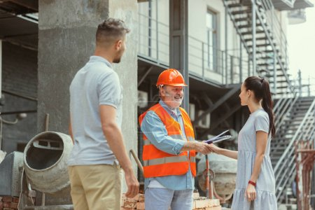 Photo for Foreman or achitect engineer shows future house, office or store design plans to a young couple. Meeting at the construction site to talk about facade appearance, interior decoration, home layout. - Royalty Free Image