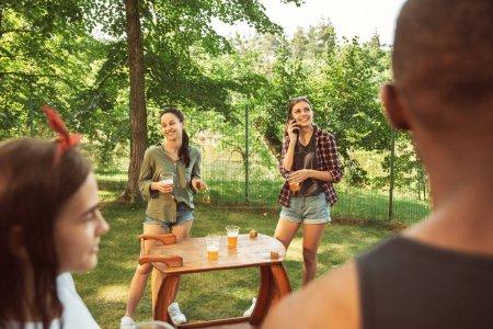 Photo pour Groupe d'amis heureux ayant bière et barbecue partie à la journée ensoleillée. Se reposer ensemble en plein air dans une clairière ou une arrière-cour forestière. Célébrer et se détendre, rire. Style de vie d'été, concept d'amitié . - image libre de droit