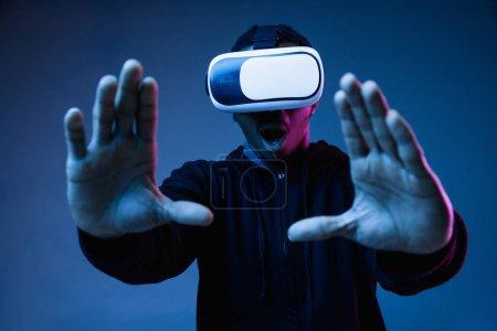 Photo pour Jeune homme afro-américain en lunettes VR au néon sur fond bleu. Portrait masculin. Concept d'émotions humaines, expression faciale, gadgets et technologies modernes. Toucher quelque chose dans le gameplay . - image libre de droit