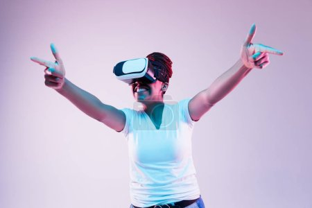 Photo for Portrait of young african-american womans playing in VR-glasses in neon light on gradient background. Concept of human emotions, facial expression, modern gadgets and technologies. Pointing on. - Royalty Free Image
