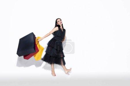 Photo pour Jeune femme brune en robe noire faisant du shopping sur fond blanc. Modèle féminin caucasien attrayant. Finance, vendredi noir, cyber lundi, ventes, concept d'automne. Copyspace. Souriant, semble heureux . - image libre de droit