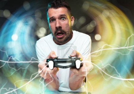 Photo for Enthusiastic gamer. Joyful young man holding a video game controller being full of emotions isolated on colorful background. Caucasian player. Getting crazy. Has the worst team in videogame. - Royalty Free Image