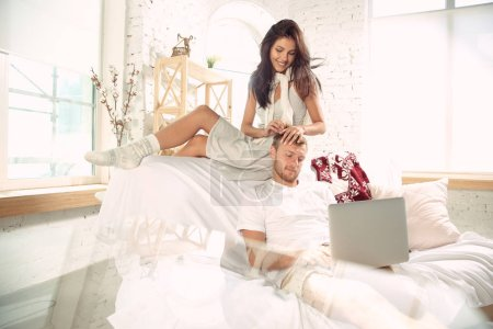 Photo for Couple of lovers at home relaxing together. Caucasian man and woman having weekend, looks tender and happy. Concept of relations, family, autumn and winter comfort. Watch cinema or buy things online. - Royalty Free Image