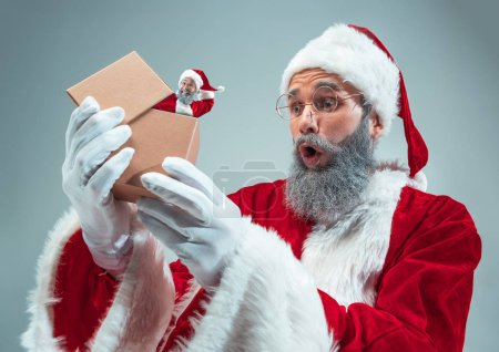 Photo for Happy Christmas Santa Claus on grey studio background. Caucasian male model in traditional holidays costume. Concept of holidays, new years, winter mood, gifts. Unpacking gifts, wondered. - Royalty Free Image