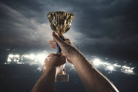 Award of victory, male hands tightening the cup of winners against cloudy dark sky