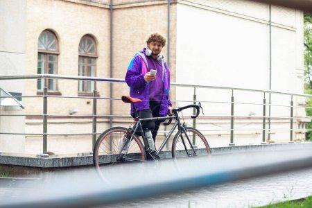 Photo pour Beau jeune homme utilisant téléphone portable et écouteurs tout en se tenant près de son vélo. Écoutez de la musique, faites défiler les nouvelles, bavardez, parlez avec des amis en déplacement. Tous les services dans l'appareil n'importe où . - image libre de droit