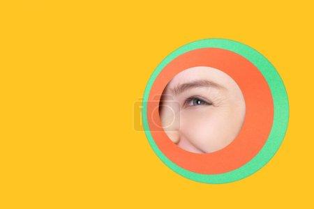 Weibliches Auge blickt durch Kreis auf gelbem Hintergrund