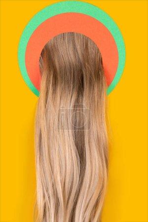 Weibliche lange Haare gucken durch Kreis in gelbem Hintergrund