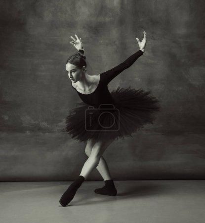 Photo pour Le mouvement artistique. Ballerine classique gracieuse dansant, posant isolée sur fond de studio sombre. Élégance tutu noir. Grace, mouvement, action et concept de mouvement. Elle a l'air en apesanteur, flexible. À la mode . - image libre de droit