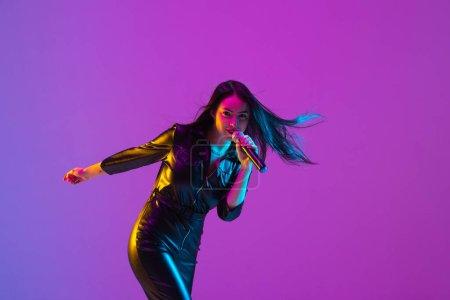 Photo pour Portrait de chanteuse caucasienne isolé sur fond de studio violet au néon. Magnifique modèle féminin en noir avec microphone. Concept d'émotions humaines, expression faciale, publicité, musique, art . - image libre de droit