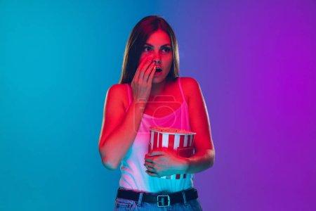 Photo pour Effrayé, mangeant du pop-corn. Portrait de jeunes femmes caucasiennes sur fond dégradé au néon. Belle mannequin féminine. Concept d'émotions humaines, expression faciale, vente, annonce, film, cinéma. - image libre de droit
