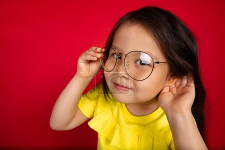 Photo for Gossip, listening to secrets. Beautiful little girl isolated on red background. Portrait of happy child gesturing. Cute asian girl in yellow wear. Concept of facial expression, human emotions - Royalty Free Image