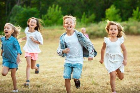 Photo pour Les enfants, les enfants qui courent sur la prairie en été. Regardez heureux, joyeux avec des émotions lumineuses sincères. Mignons garçons et filles caucasiens. Concept d'enfance, bonheur, mouvement, famille et été. - image libre de droit