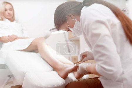 Podiatrist doctor in white making polish procedure for foot.