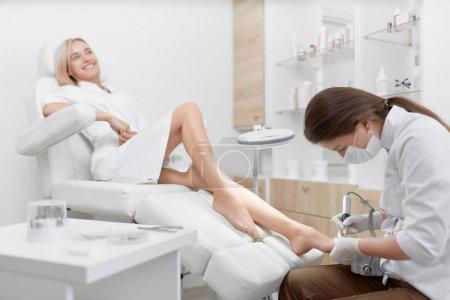 Photo pour Femme blonde souriante se détendant au salon de beauté, se souciant de sa santé et de ses pieds. Femme podiatre médecin faisant la procédure pour le pied avec un équipement spécial pour le client. Concept de podiatrie et de médecine . - image libre de droit
