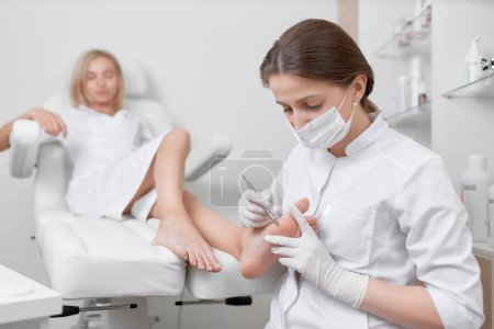 Photo pour Vue du client féminin felaxing dans le fauteuil lorsque le médecin podiatre faisant la procédure pour éplucher les pieds avec un outil de fer. Service professionnel de podiatrie et concept médical . - image libre de droit