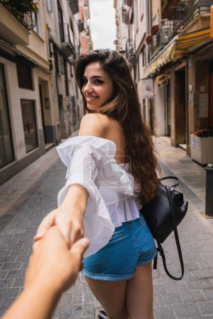 Rückseite der schönen jungen Dame charmant lächelnd und Hand der Ernte Person beim Gehen auf der Straße von Valencia in Spanien