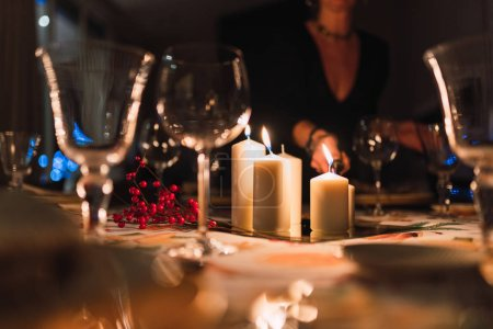 Photo for Faceless woman in dark room lighting white candles on table prepared for holiday evening dinner - Royalty Free Image