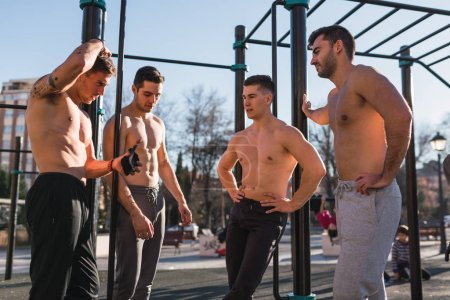 Photo pour Vue latérale de jeunes sportifs torse nu gars parler et se reposer près du menton jusqu'à bars dans la salle de gym en plein air dans la journée ensoleillée - image libre de droit