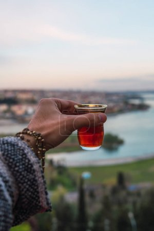 Photo for From above hand holding cup of red wine against beautiful landscape of Istanbul - Royalty Free Image